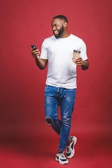 Retrato de comprimento total de bonito homem afro-americano com telefone móvel e tirar a xícara de café. isolado sobre o fundo vermelho.