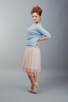 Retrato de comprimento total de jovem encaracolado ruivo na blusa azul e saia rosa