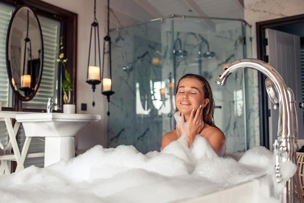Retrato de comprimento total de linda mulher caucasiana soprando espuma enquanto toma banho relaxante