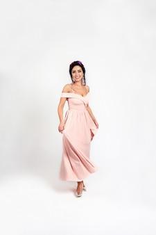 Retrato de comprimento total de morena jovem bonito vestido rosa na moda com um aro de primavera com flores na cabeça dela.