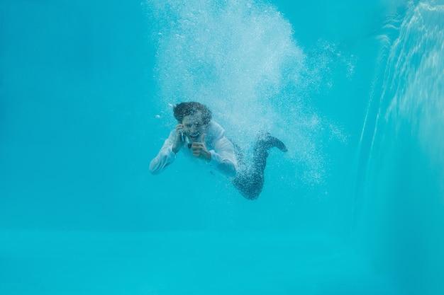 Retrato de comprimento total de um jovem a nadar debaixo de água