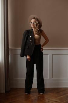 Retrato de comprimento total de uma linda modelo feminina, vestindo roupas da moda e óculos de sol da moda na cl ...