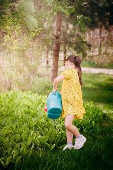 Retrato de comprimento total de uma menina regando lírios do vale de um regador uma vista traseira de uma menina.