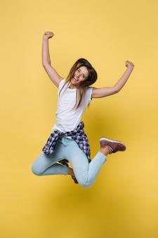 Retrato de comprimento total de uma mulher caucasiana casual alegre pulando