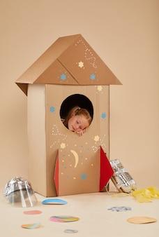 Retrato de comprimento total vertical de uma menina bonitinha sonhando com espaço dentro de um foguete de papelão