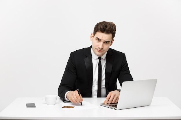 Retrato de conceito de negócio concentrado jovem empresário de sucesso, escrevendo documentos na bright offi ...