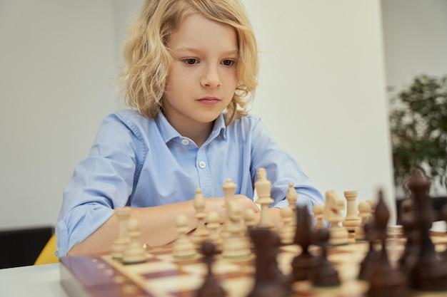 Retrato de concentração de um menino caucasiano focado em uma camisa azul, sentado na sala de aula e pensando