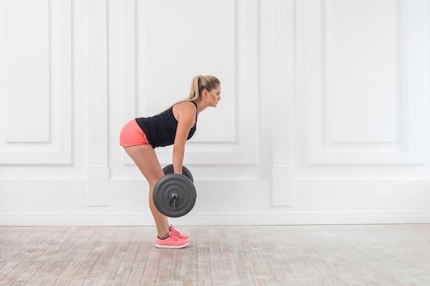 Retrato de concentração de vista lateral de mulher jovem atlética bonita fisiculturista em shorts rosa e blusa preta, fazendo agachamentos e exercitando o músculo glúteo na academia com a barra na parede branca. interior