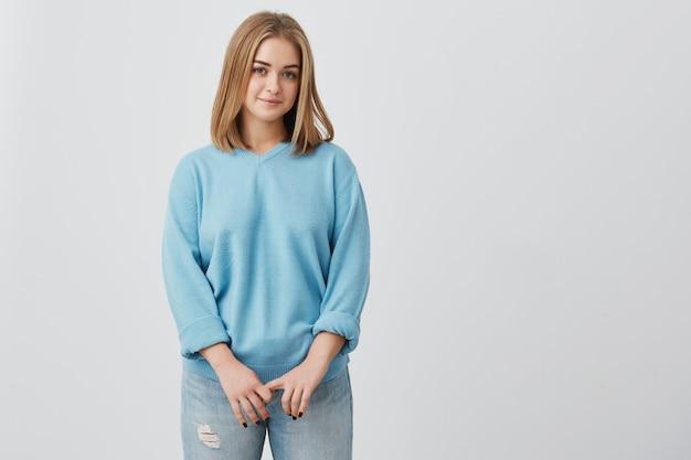 Retrato de concurso europeu loira jovem com a pele saudável, vestindo blusa azul e calça jeans, olhando com expressão calma ou agradável. modelo de mulher caucasiana com cabelo loiro, posando dentro de casa