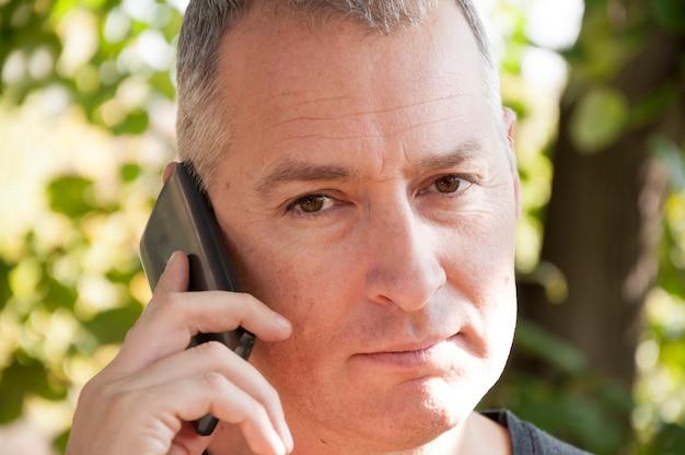 Retrato, de, confiante, bonito, cinzento, homem cabelo, parque, falando, sobre, seu, telefone móvel