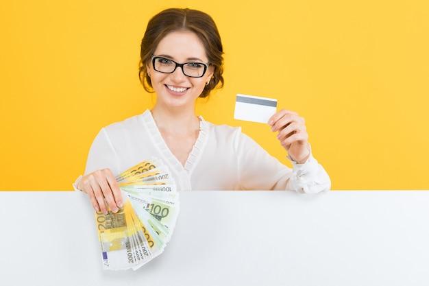 Retrato, de, confiante, bonito, jovem, mulher negócio, com, dinheiro, e, cartão crédito, em, dela, mãos, com, experiência vazia