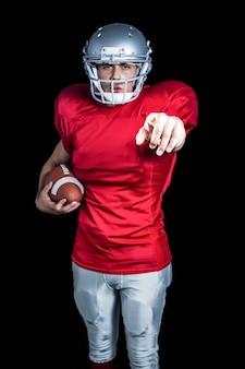 Retrato, de, confiante, desportista, apontar, enquanto, segurando, futebol americano