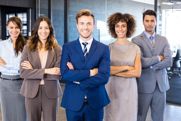 Retrato, de, confiante, equipe negócio, ficar, em, escritório, com, seu, mãos cruzaram
