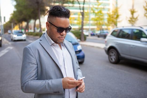 Retrato, de, confiante, homem negócios, em, óculos de sol, com, smartphone