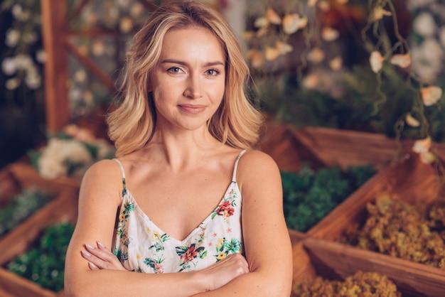 Retrato, de, confiante, mulher jovem, com, braços cruzaram, olhando câmera