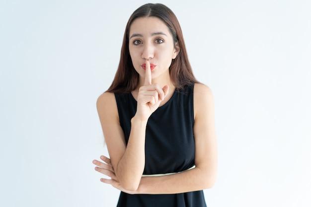 Retrato, de, confiante, mulher jovem, ficar, com, dedo, ligado, lábios