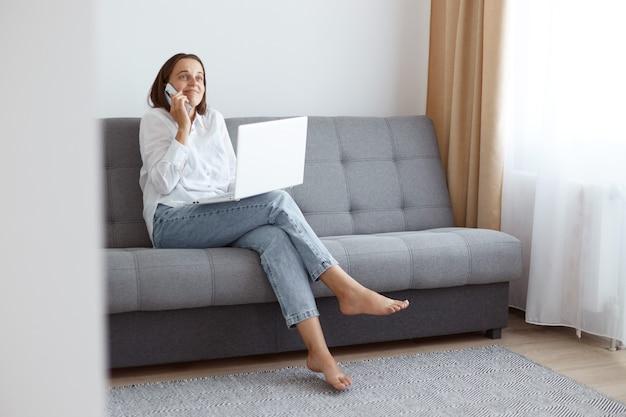 Retrato de confuso positivo jovem adulto feminino freelancer, vestindo jeans e camisa branca estilo casual, sentado no sofá cinza com o laptop, falando ao telefone enquanto trabalhava online.