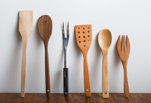 Retrato de conjunto de utensílios de cozinha em mesa de madeira com fundo branco