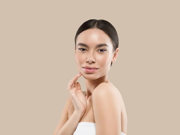 Retrato de corpo de rosto de beleza de mulher ásia tocando sua pele de rosto saudável. cor de fundo. marrom