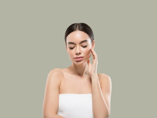Retrato de corpo de rosto de beleza de mulher ásia tocando sua pele de rosto saudável. cor de fundo. verde