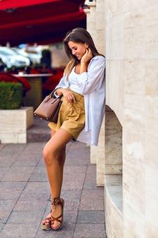 Retrato de corpo inteiro ao ar livre da deslumbrante modelo morena bronzeada, vestindo shorts bege de linho, bolsa luxuosa de couro caramelo, camisa branca e acessórios dourados, caminhando pelas ruas de paris.