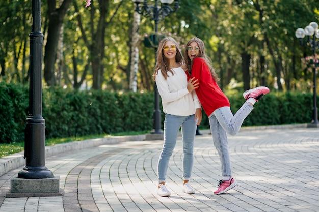 Retrato de corpo inteiro ao ar livre de duas garotas muito amigáveis e felizes se divertindo e caminhando juntas após o estudo na cidade, dia ensolarado, emoções boas e verdadeiras, humor engraçado
