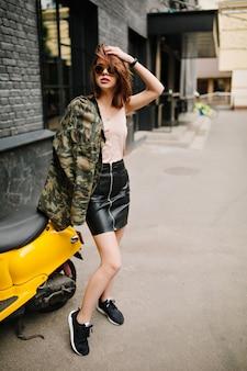 Retrato de corpo inteiro ao ar livre de uma garota graciosa de cabelos escuros usando jaqueta militar e tênis preto