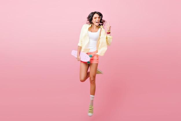 Retrato de corpo inteiro da adorável modelo feminina hispânica em shorts jeans se divertindo. foto de pular senhora morena com casaco amarelo, segurando o skate.