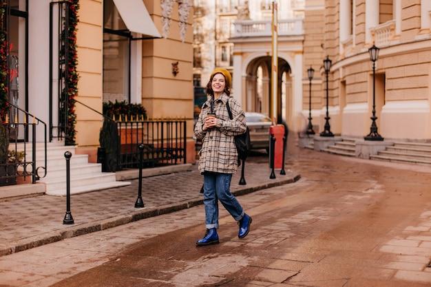 Retrato de corpo inteiro da aluna andando no centro da cidade. mulher em sapatos azuis