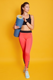 Retrato de corpo inteiro da bela jovem atlética segurando o tapete de ioga nas mãos, olhando de lado, pronto para malhar