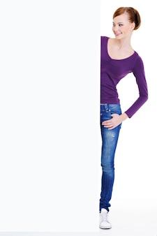 Retrato de corpo inteiro da bela jovem europeia em pé perto de um outdoor de publicidade