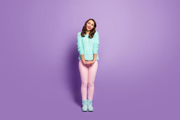 Retrato de corpo inteiro da bela senhora bonita penteado encaracolado de bom humor, procure o sonhador do espaço vazio usar sapatos de calça rosa suéter pastel fofo.