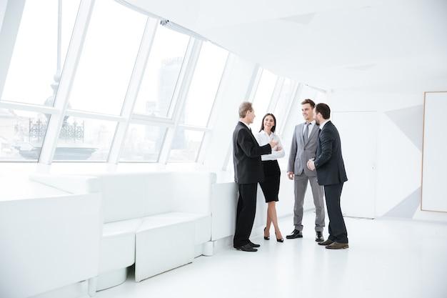 Retrato de corpo inteiro da equipe de negócios em pé perto da janela na sala de conferências