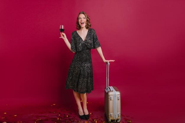 Retrato de corpo inteiro da graciosa modelo feminina branca bebendo vinho antes da viagem