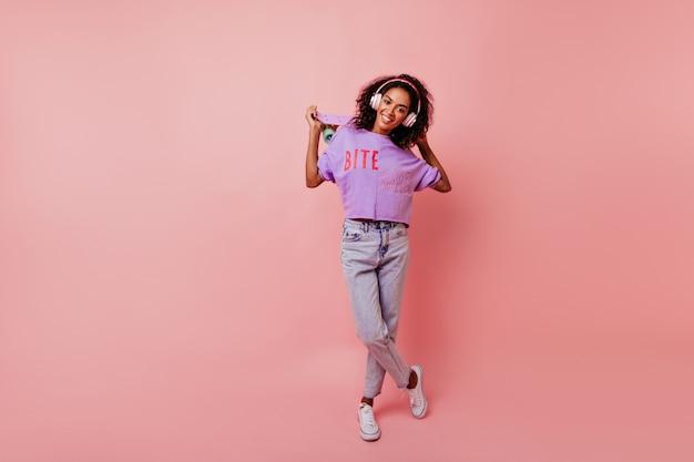 Retrato de corpo inteiro da incrível senhora africana em jeans segurando o skate. elegante garota negra em fones de ouvido e camisa roxa em pé rosa.