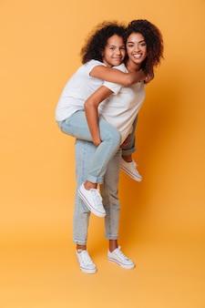 Retrato de corpo inteiro da menina africana sorridente, carregando a irmã