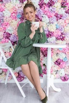 Retrato de corpo inteiro da menina loira se senta à mesa, contra um fundo floral com café