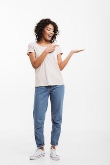 Retrato de corpo inteiro da mulher americana 20 anos vestindo jeans e camiseta demonstrando copyspace texto ou produto na palma da mão, isolado sobre a parede branca