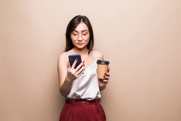 Retrato de corpo inteiro da mulher asiática sorridente usando telefone celular enquanto segura a xícara de café para ir isolado sobre a parede bege