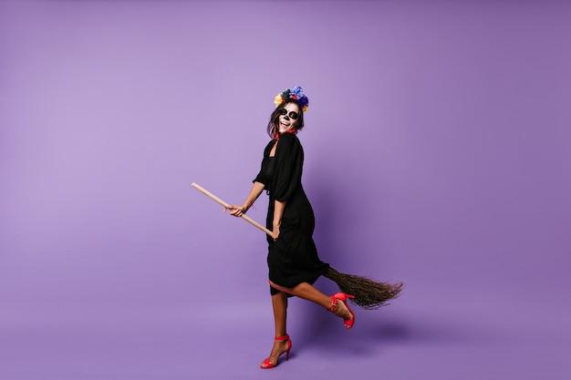 Retrato de corpo inteiro da noiva morta dançando no halloween. bruxa morena animada sentada na vassoura.
