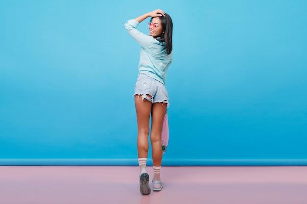 Retrato de corpo inteiro da parte de trás de uma garota hispânica esportiva em shorts da moda. mulher brincalhona de cabelos negros com pele bronzeada olhando por cima do ombro.