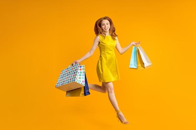 Retrato de corpo inteiro da ruiva, mulher de sorte em um vestido amarelo pulando, se divertindo com pacotes de compras em mãos, regozijando-se isoladas sobre um fundo de cor amarela brilhante no estúdio.