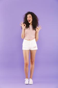 Retrato de corpo inteiro de adolescente com cabelos cacheados no verão usar sorrindo e mostrando sinal ok
