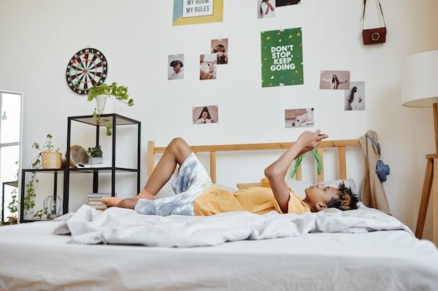 Retrato de corpo inteiro de adolescente mestiço deitado na cama e usando o smartphone, copie o espaço