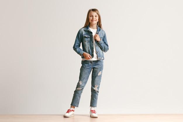 Retrato de corpo inteiro de adolescente pequeno bonito em roupas elegantes jeans sorrindo