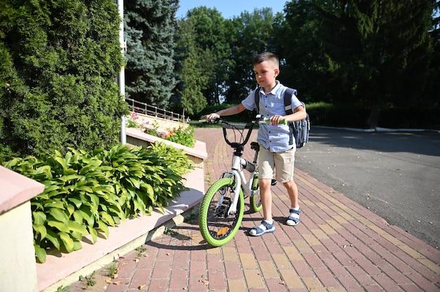 Retrato de corpo inteiro de adorável criança estacionando sua bicicleta na entrada da escola. garoto bonito voltando para a escola
