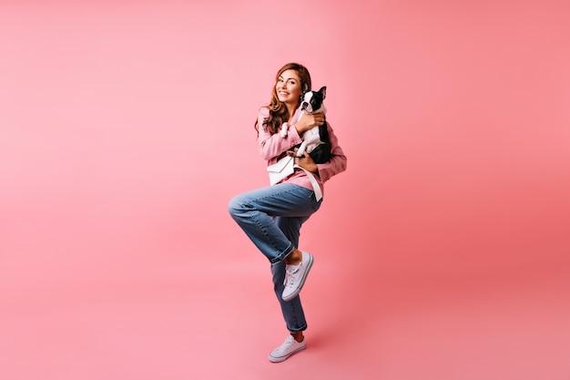 Retrato de corpo inteiro de adorável garota em jeans da moda segurando bulldog francês. mulher caucasiana sonhadora posando com seu cachorro na rosa.