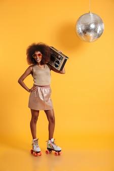 Retrato de corpo inteiro de alegre mulher discoteca africana com a mão na cintura, vestindo roupas retrô em pé sobre patins, segurando o boombox