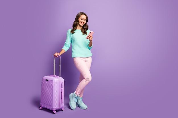 Retrato de corpo inteiro de alegre senhora esperando o registro do aeroporto inclinar-se no telefone de navegação mala de rolamento usar sapatos de calça rosa pastel de suéter difuso.