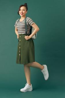 Retrato de corpo inteiro de aluna sorridente com mochila andando de lado sobre fundo verde